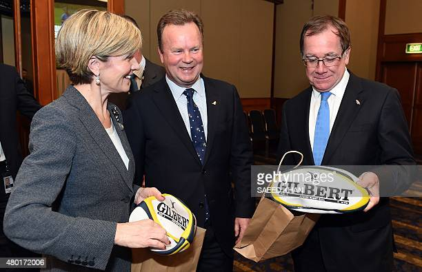 Australian Foreign Minister Julie Bishop gives a rugby ball to her New Zealand counterpart Murray McCully as Australia Rugby Union CEO Bill Pulver...