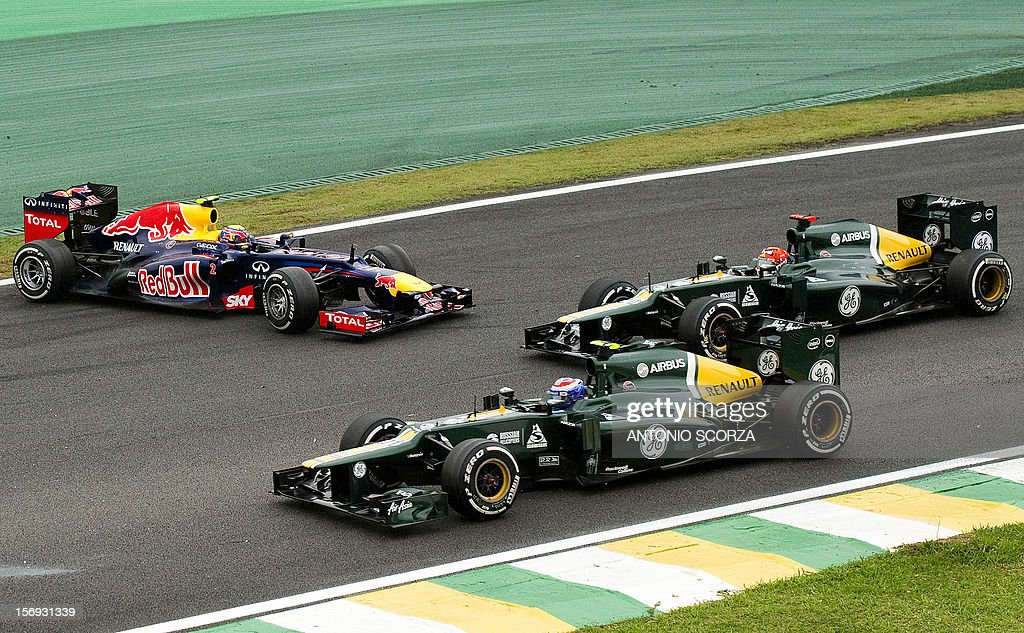 Australian Formula One driver Mark Webber (L) loses control of his RedBull car as he is overtaken by Kimi Raikkonen and Romain Grosjean of Lotus on November 25, 2012 during the Brazil F-1 GP at the Interlagos racetrack in Sao Paulo, Brazil.