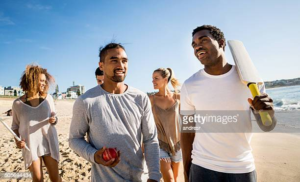 australian friends playing cricket at the beach - sport of cricket stock pictures, royalty-free photos & images
