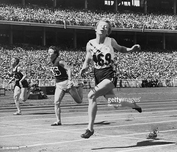 Australian Girl on Way to Gold Medal. Melbourne, Australia: Symmetry in motion is displayed by Shirley Strickland of Australia, Maria Golubnichaia of...