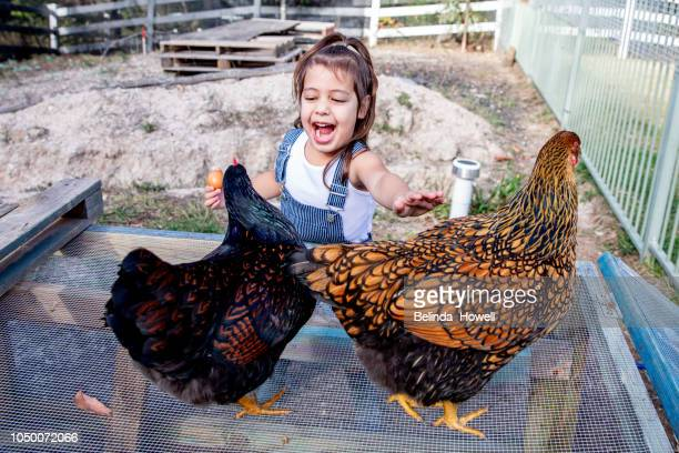 Australian girl plays with her pet chicken and poses in her rural backyard