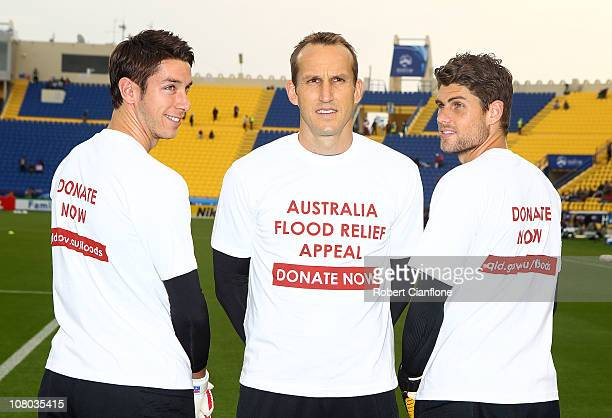Australian goalkeepers Brad Jones Mark Schwarzer and Nathan Coe poes with tshirts which show their support for flood victims in Queensland Australia...
