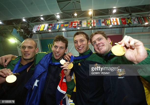 Australian gold medalist swimmers Todd Pearson Grant Hackett Ian Thorpe Asheley Callus celebrate on the podium after the 2002 Manchester Commonwealth...