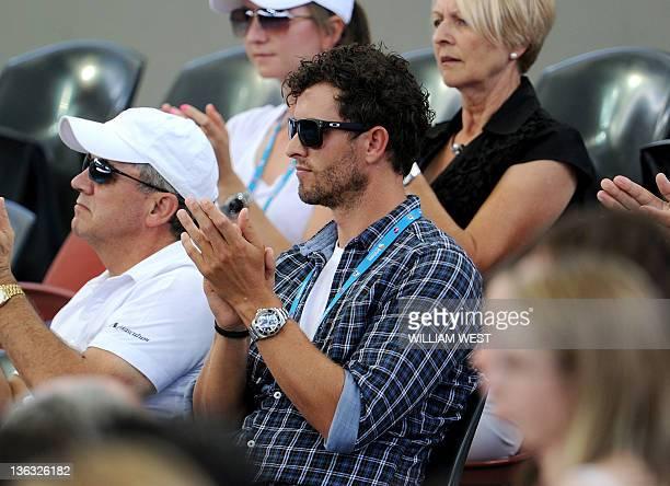 Australian golfer Adam Scott watches girlfriend Ana Ivanovic of Serbia during her first round match against Tamira Paszek of Austria at the Brisbane...
