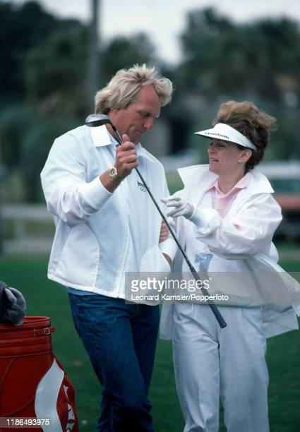 Australian golfer Greg Norman hands his wife Laura Andrassy a driver circa 1987