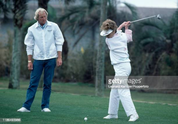 Australian golfer Greg Norman watches as his wife Laura Andrassy hits a tee shot circa 1987