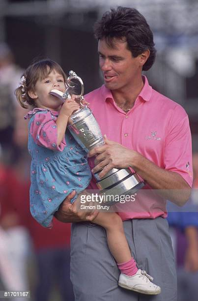 Australian golfer Ian BakerFinch lets his daughter suck on the trophy after winning the British Open Championship at the Royal Birkdale golf course...