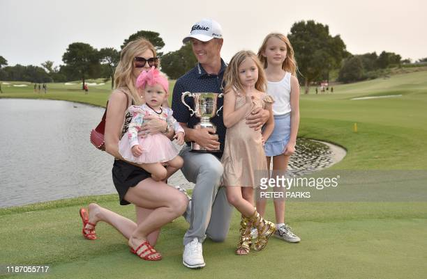 Australian golfer Matt Jones holds the trophy surrounded by his family after winning the Australian Open golf tournament at the Australian Golf Club...