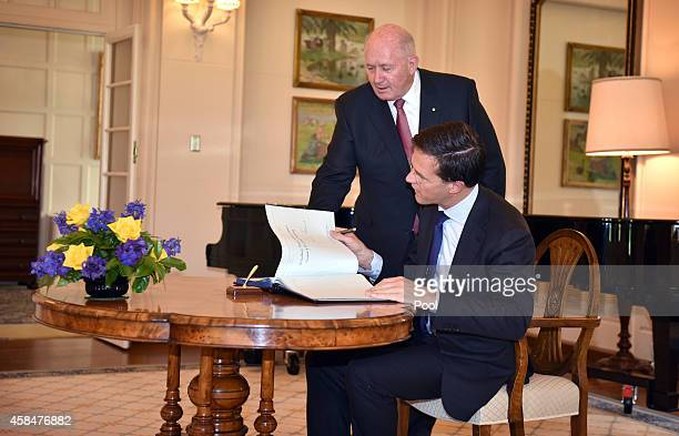 Australian GovernorGeneral Peter Cosgrove assists as the Netherlands Prime Minister Mark Rutte signs the visitors book at Government House in on...