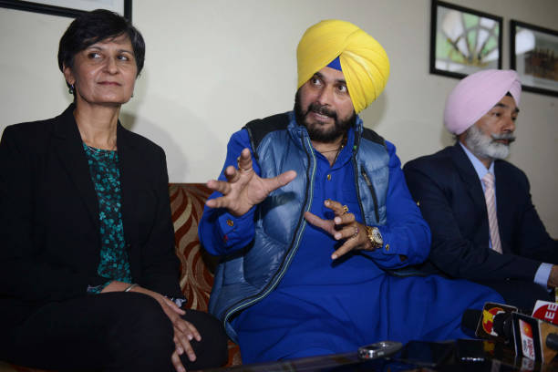 Australian High Commissioner to India Harinder Sidhu looks on as Punjab Cabinet Minister Navjot Singh Sidhu speaks during a press conference after...
