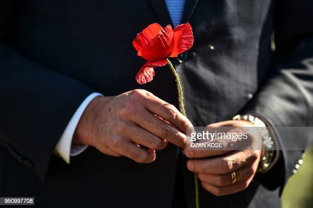 Australian Home Affairs Minister Peter Dutton holds a poppy flower during a ceremony marking the 103rd anniversary of ANZAC Day at Lone Pine Cemetery...
