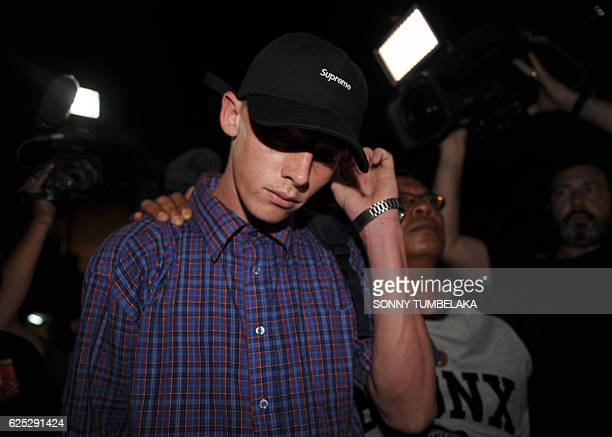 Australian Jamie Murphy is escorted by police during his release at a police station in Kuta on Indonesia's resort island of Bali on November 23 2016...