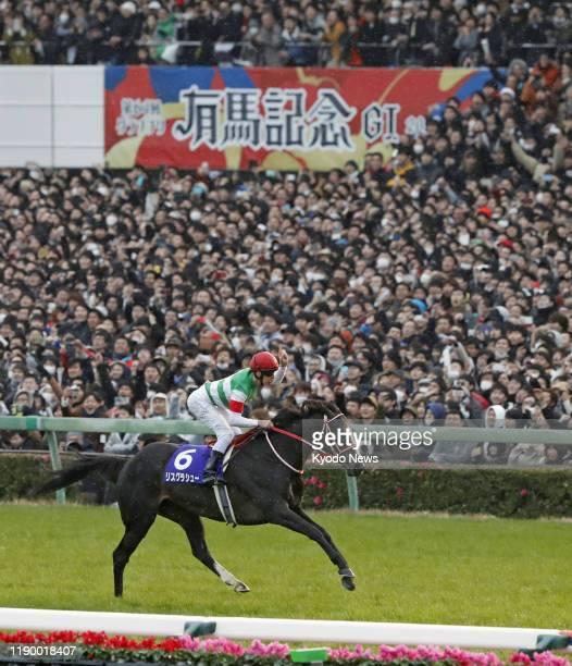 Australian jockey Damian Lane reacts after steering Lys Gracieux to the Grade 1 title at the 64th Arima Kinen at Nakayama Racecourse near Tokyo on...