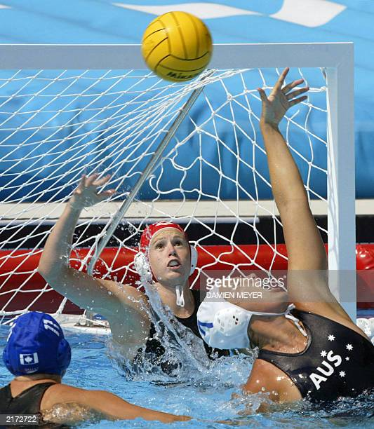 Australian Jodie Stuhmcke and goalkeeper Emma Knox intercept the ball in front of Canadian Valerie Dionne during their water polo preliminary match...