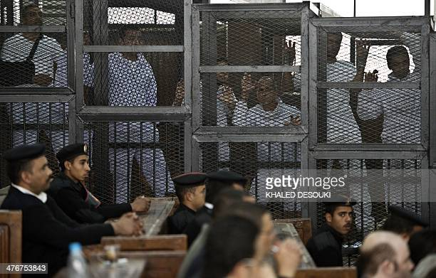 Australian journalist Peter Greste of AlJazeera and his colleagues stand inside the defendants cage during their trial for allegedly supporting the...