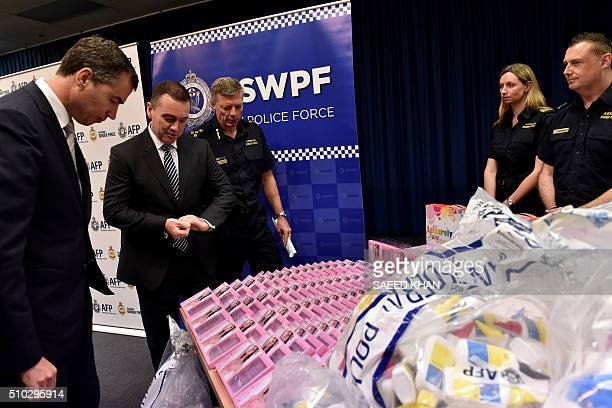 Australian Justice Minister Michael Keenan examines gel bra inserts containing concealed crystal methamphetamine with Australian Federal Police State...