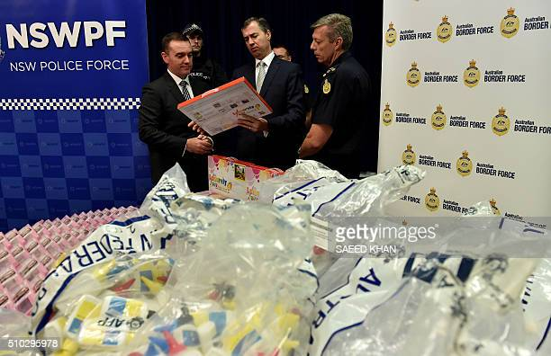 Australian Justice Minister Michael Keenan examines product packaging containing concealed crystal methamphetamine with Australian Federal Police...