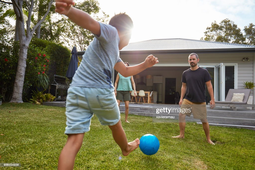 Australian kid playing with parents in the back yard garden : Stock Photo