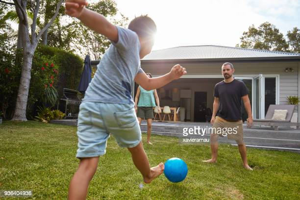 australian kid playing with parents in the back yard garden - sports ball stock pictures, royalty-free photos & images
