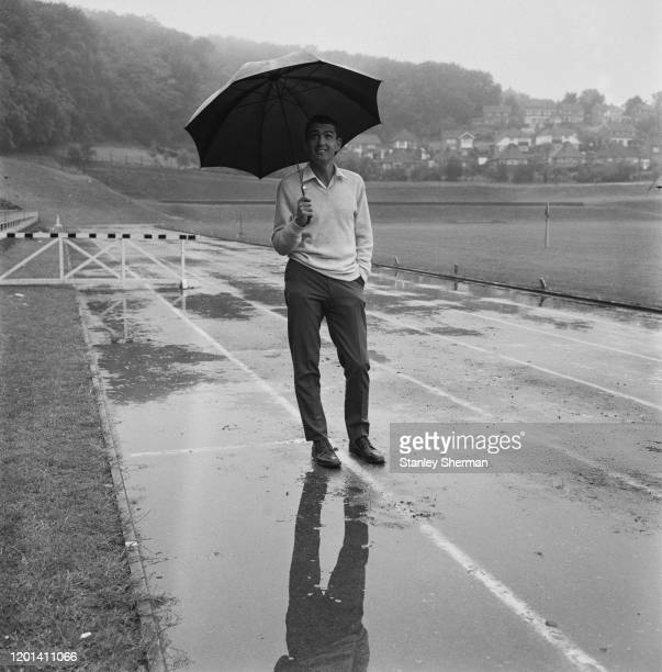 Australian long-distance runner Ron Clarke sheltering from the rain beneath an umbrella on a sodden running track at the Withdean Stadium in...