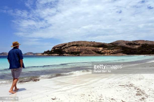 australian man walking along lucky bay in western australia - rafael ben ari stock-fotos und bilder