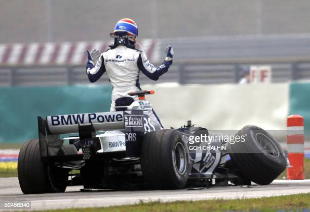 Australian Mark Webber of BMW Williams gestures to Italian Giancario Fisichella of Renault after they crash out of the Formula One Malaysian Grand...