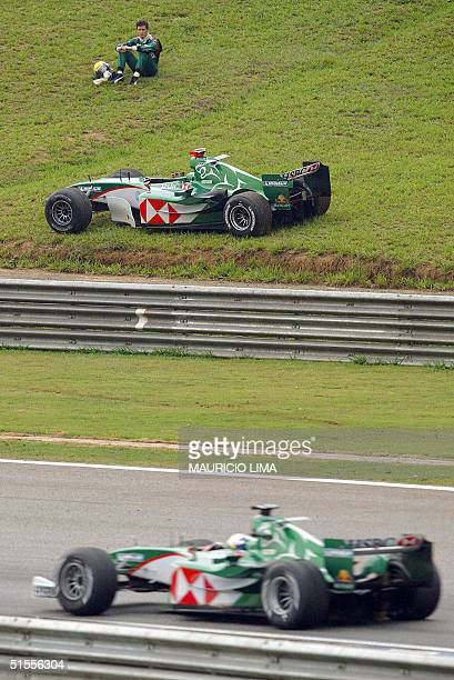 Australian Mark Webber of Jaguar -sitting on the grass- watches his teammate Austrian Christian Klien passing by, after abandoning Brazil's F1 GP 24...