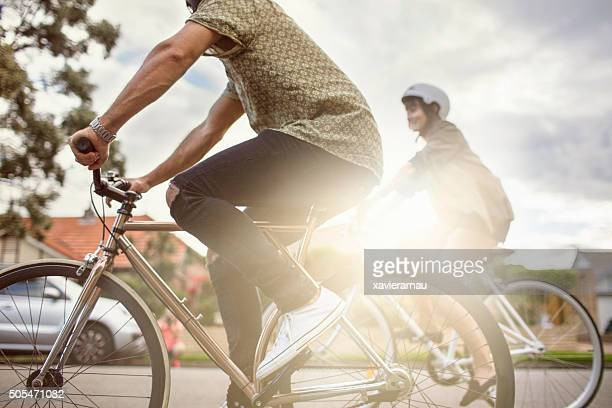 australian mid adult couple riding bikes back home - sustainability stock photos and pictures