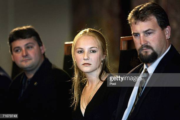 Australian miners Brant Webb and Todd Russell sit with Lauren Kielmann the daughter of late miner Larry Knight as they listen to speeches at a...