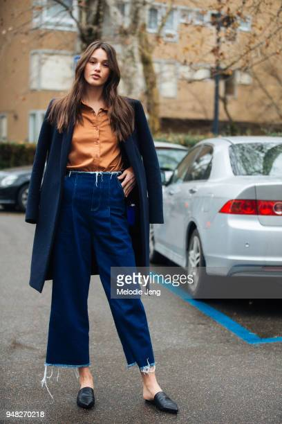 Australian model Aleyna Fitzgerald wears a blue peacoat an orange top jeans and black loafers during Milan Fashion Week Fall/Winter 2018/19 on...
