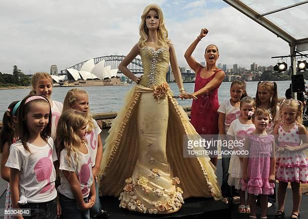 Australian model Erika Heynatz cuts a 21 metre high 'Barbie doll' chocolate mud cake to celebrate the 50th anniversary of the world's most popular...