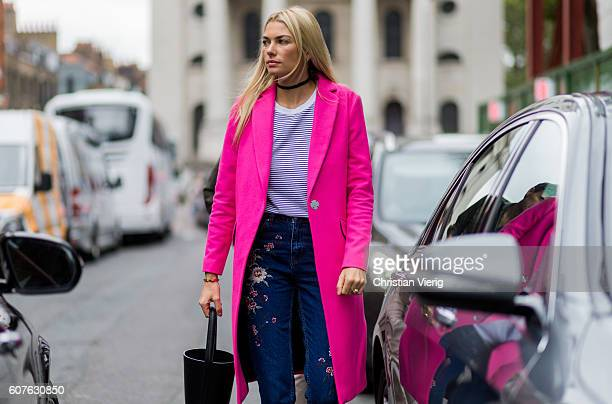 Australian model Jessica Hart wearing a pink wool coat dark denim jeans with patches bucket bag and blue white striped tshirt outside Topshop during...