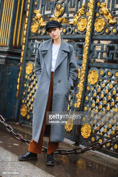 Australian model Maisie Dunlop wears a newsboy cap a long gray coat white tshirt light brown corduroy pants and black boots after the Givenchy show...