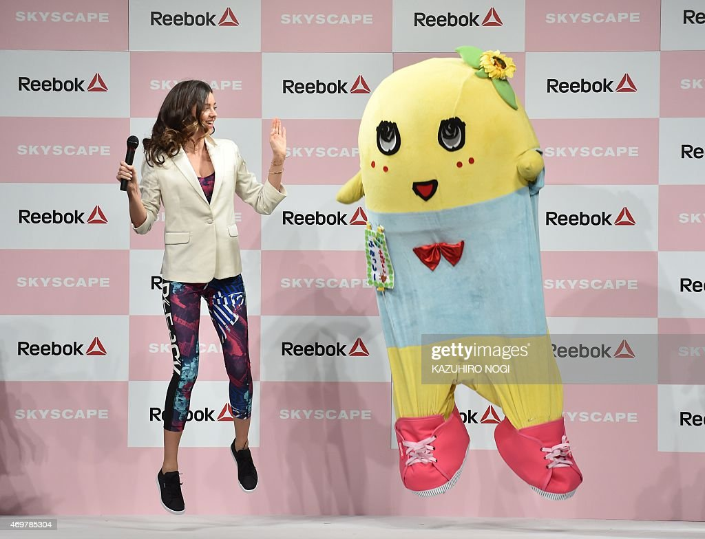 Australian model Miranda Kerr (L) performs with 'pear fairy' Funassyi, the unofficial mascot of the city of Funabashi in suburban Tokyo, as she takes part in a promotional event during her visit on April 15, 2015. The 31-year-old model reportedly arrived the day during her promotional tour in Asia.