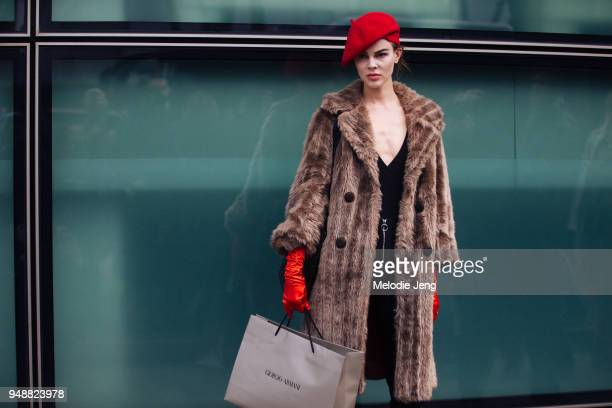 Australian model Ruby Jean Wilson wears a red beret brown fur coat black slip dress and long red silk gloves after the Armani show during Milan...