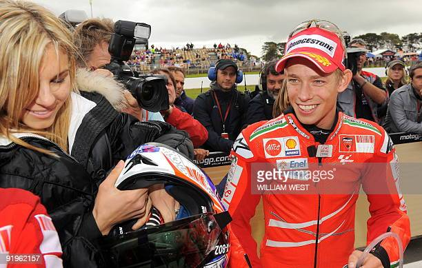 Australian MotoGP rider Casey Stoner smiles as he hands his helmet to his wife Adriana after claiming pole position on his Ducati for the Australian...