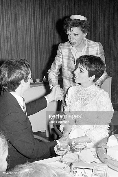 Australian musician Peter Allen sits with his new wife, actress and singer Liza Minnelli, at their wedding and holds hands with Minnelli's mother,...