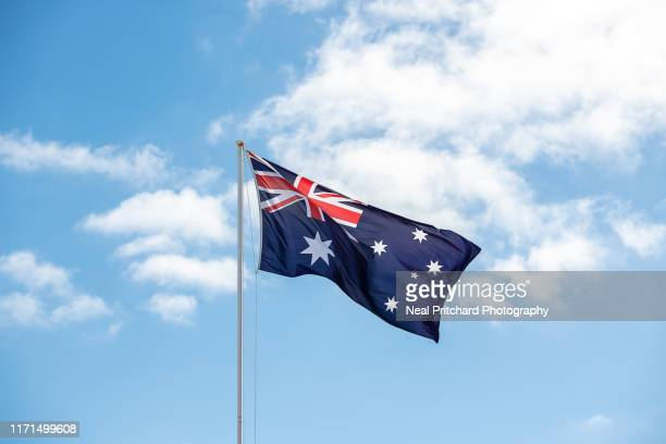 australian national flag being flown against a perfect blue sky in summer - australian flag stock pictures, royalty-free photos & images