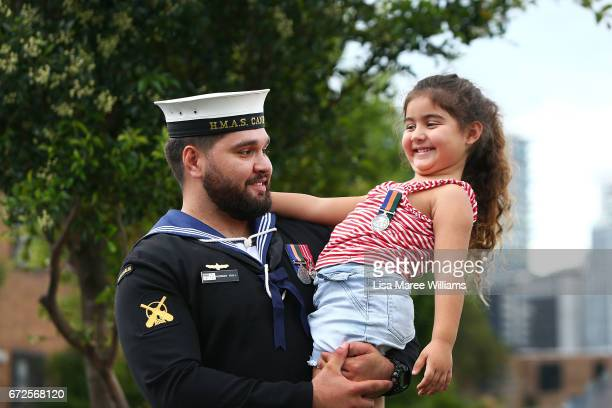 Australian Navy AB Seaman Murray Hall holds his daughter Kiarrah during a ANZAC service in Redern on April 25 2017 in Sydney Australia The annual...