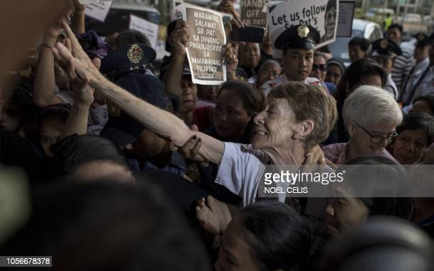 TOPSHOT Australian nun Patricia Fox is surrounded by supporters as she arrives at the departure area of the Manila International Airport on November...