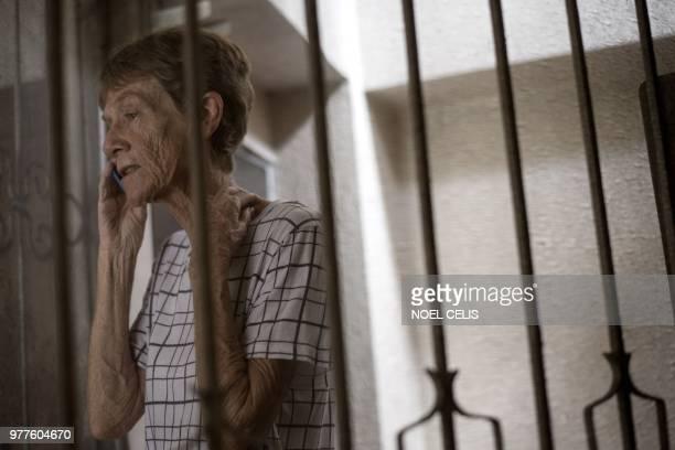 Australian nun Patricia Fox speaks on her mobile phone inside her house in Manila on June 18 2018 An Australian nun ordered to leave the Philippines...