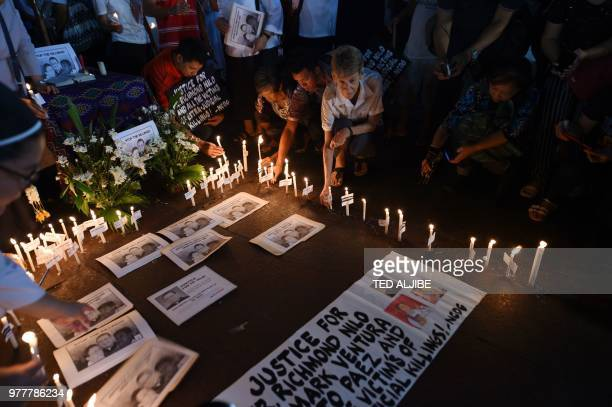 Australian nun Sister Patricia Fox holds a candle along with colleagues as she attends a prayer vigil for the killed catholic priests in front of...