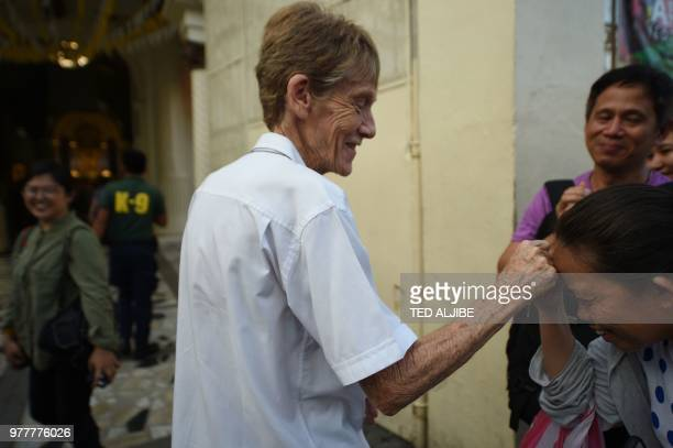 Australian nun Sister Patricia Fox is greeted by a supporter as she attends a prayer vigil for the killed catholic priests in front of Quiapo church...