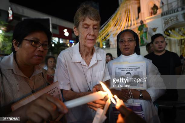 Australian nun Sister Patricia Fox lights a candle as she attends a prayer vigil for the killed catholic priests in front of Quiapo church in Manila...