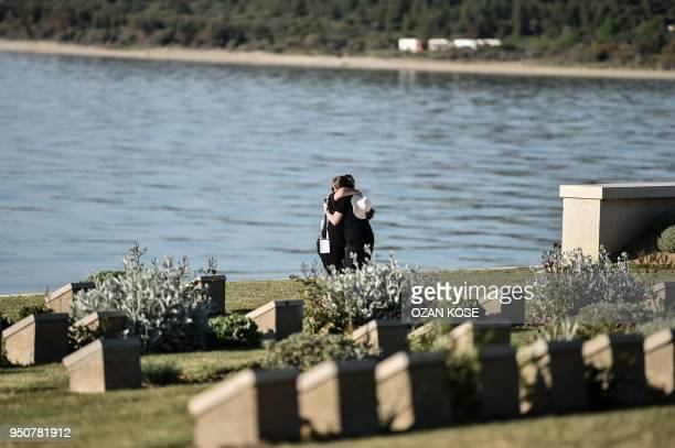 Australian officials hug each other next to the Anzac cove in Canakkale on April 24 before a ceremony marking the 103rd anniversary of ANZAC Day The...