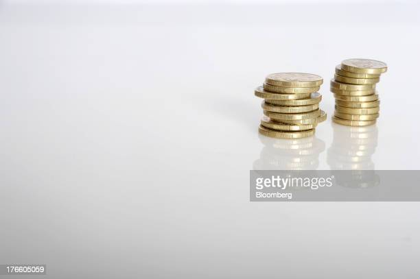 Australian onedollar coins left and twodollar coins are arranged in stacks for a photograph in Melbourne Australia on Thursday Aug 15 2013 The...