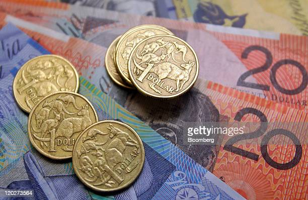 Australian onedollar coins sit with a collection of bank notes arranged for a photograph in Sydney Australia on Wednesday Aug 3 2011 Australia's...