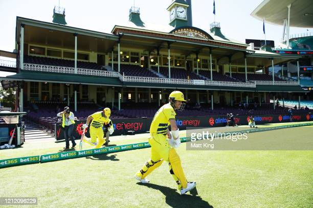 Australian openers David Warner and Aaron Finch walk onto the field to bat after Cricket Australia announced no public will be admitted to venues for...