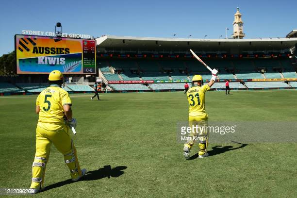Australian openers David Warner and Aaron Finch walk onto the field to bat to empty stands after Cricket Australia announced no public will be...