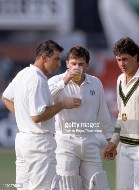 Australian opening batsmen Geoff Marsh and Mark Taylor have a drink brought on by twelfth man Tim May during their first wicket partnership of 329 in...